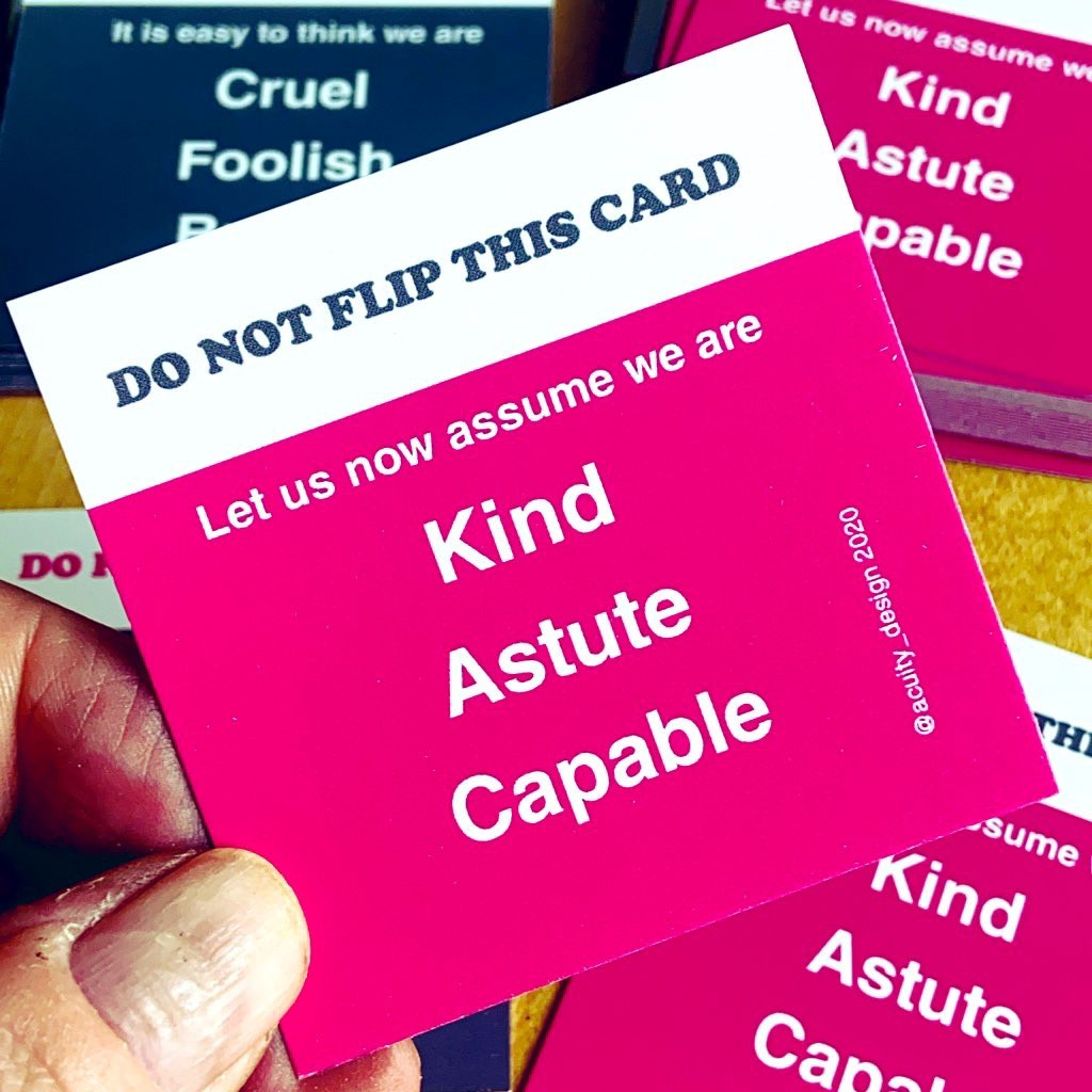Cards saying assume we Kind, Astute and capable held in hand